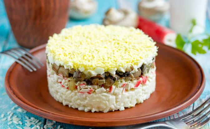 Фото еще одного слоёного салата с шампиньонами, рисом и крабовыми палочками