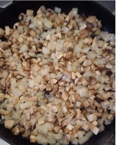 На разогретой сковороде жарим шампиньоны с луком до тех пор, пока не испарится влага от грибов.