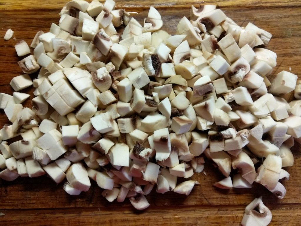 Начинаем подготавливать продукты, очищаем от тонкой кожицы шампиньоны, промываем и высушиваем грибы на бумажном полотенце.