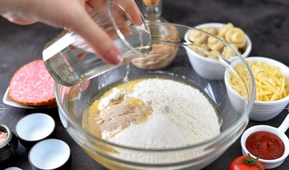 Добавьте теплую воду и начните месить тесто