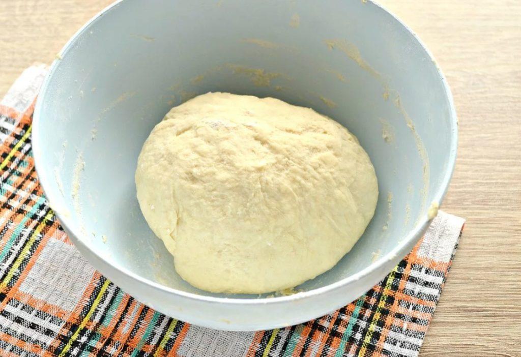 Раскатываем его в круг и смазываем соусом.