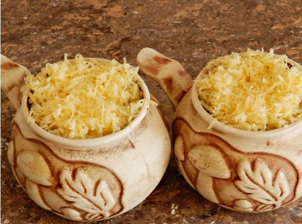 Перекладываем жульен в специальные горшки, сверху посыпаем сыром и отправляем в духовку на 10 минут.