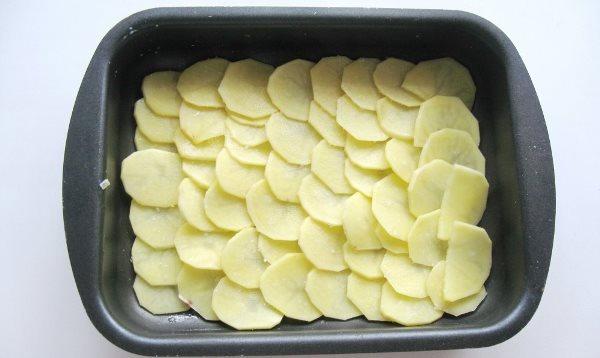 Теперь приступаем к самой важной части. Кладем нижний слой картофеля в емкость для запекания, сверху располагаем курицу с грибами и соусом.