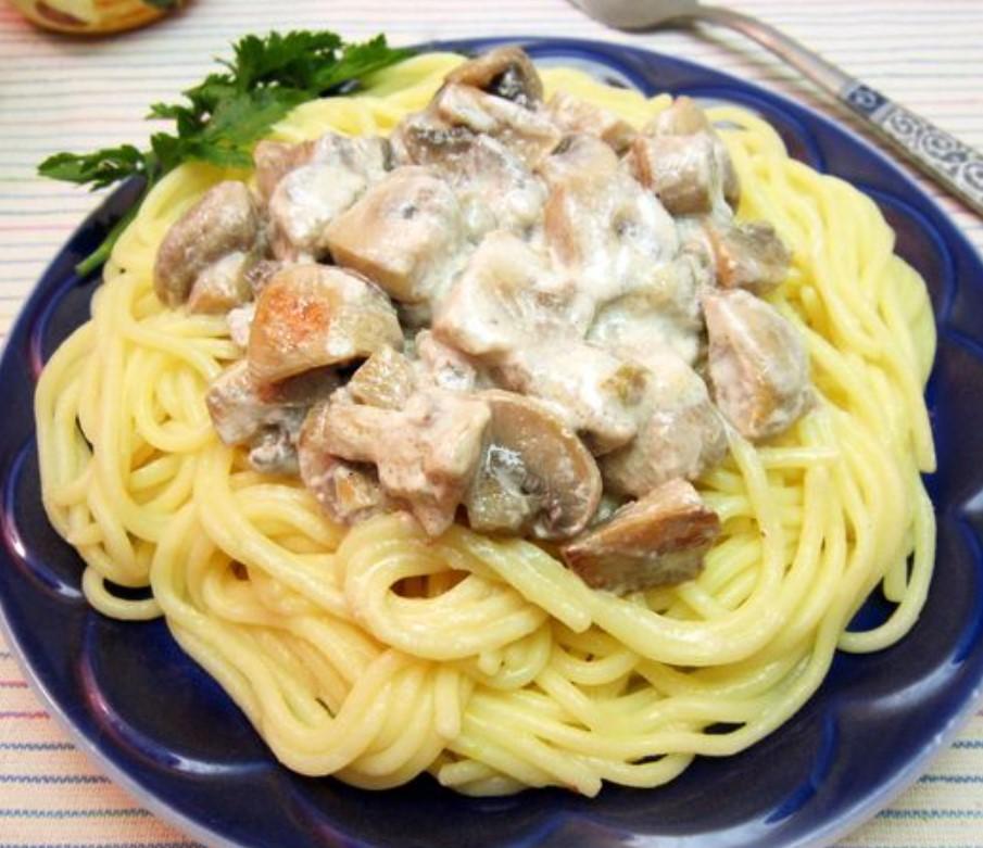 На тарелку выкладываем спагетти, а сверху сливочный соус с грибами.