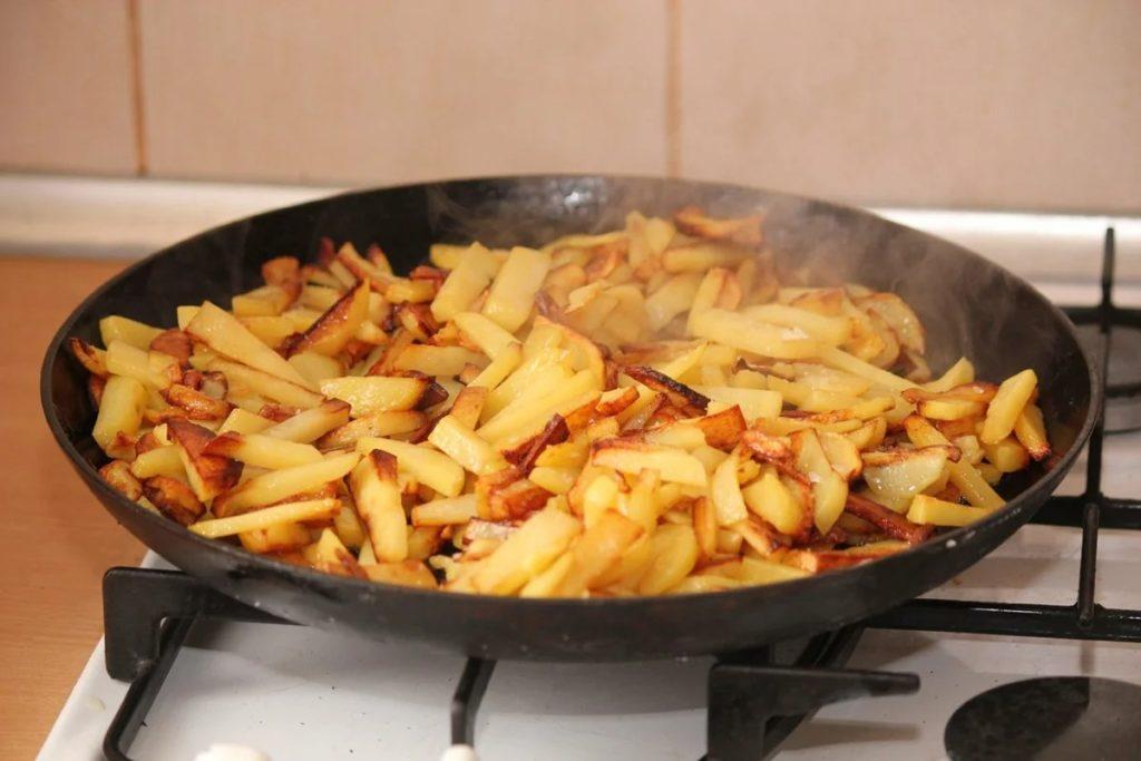 Добавить к картошке лук, тщательно перемешать и обжаривать ингредиенты в течение 5 минут